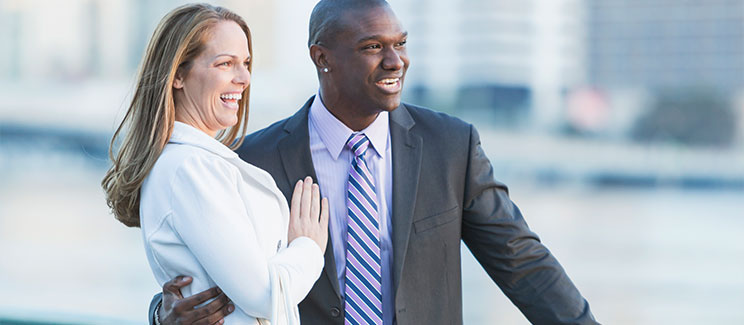 man and woman in suits on the street with arms around each other, laughing